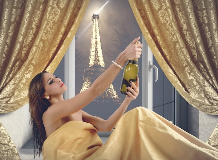 Beautiful woman with champagne in a luxury hotel room